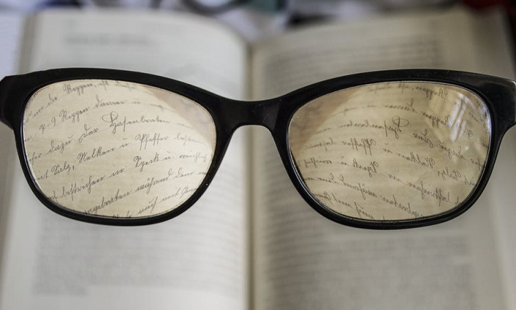 Large glasses reading a book