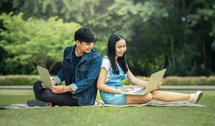 Boy and girl relaxing while using technology outside