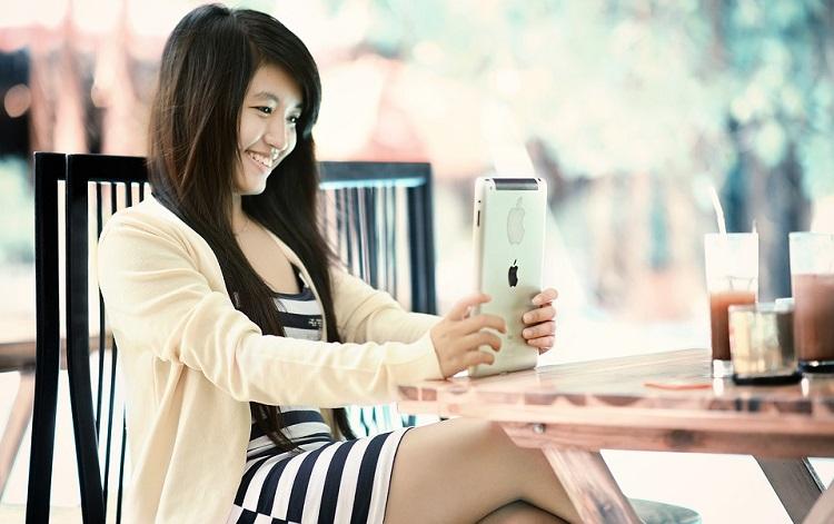 Girl smiling using an iPad