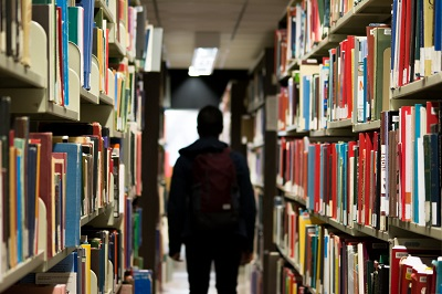 Man walking through library stacks
