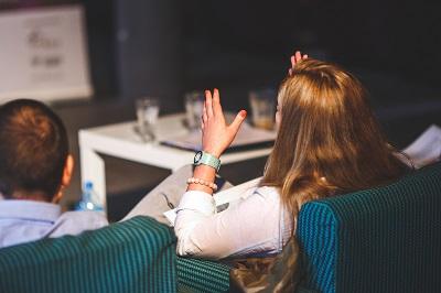 Woman raising her hand at a seminar