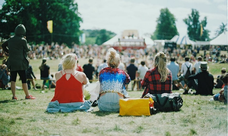 3 woman watching an outdoor concert