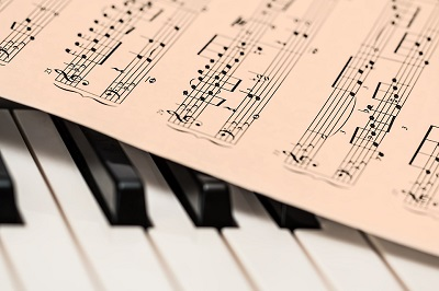 Sheet music over piano keys