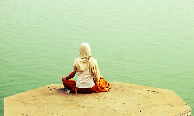 Woman meditating near the water