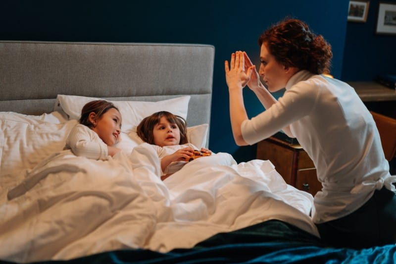 Nanny telling a story to two children in bed