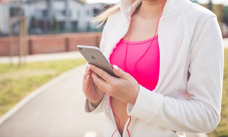 Woman in running outfit holding phone