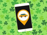 Rideshare app on smartphone, green clover background