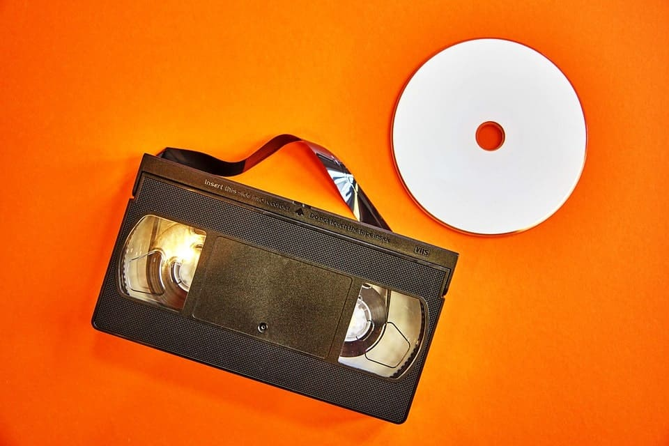 Concept of stream ripping with videocassette with tape pulled out next to DVD