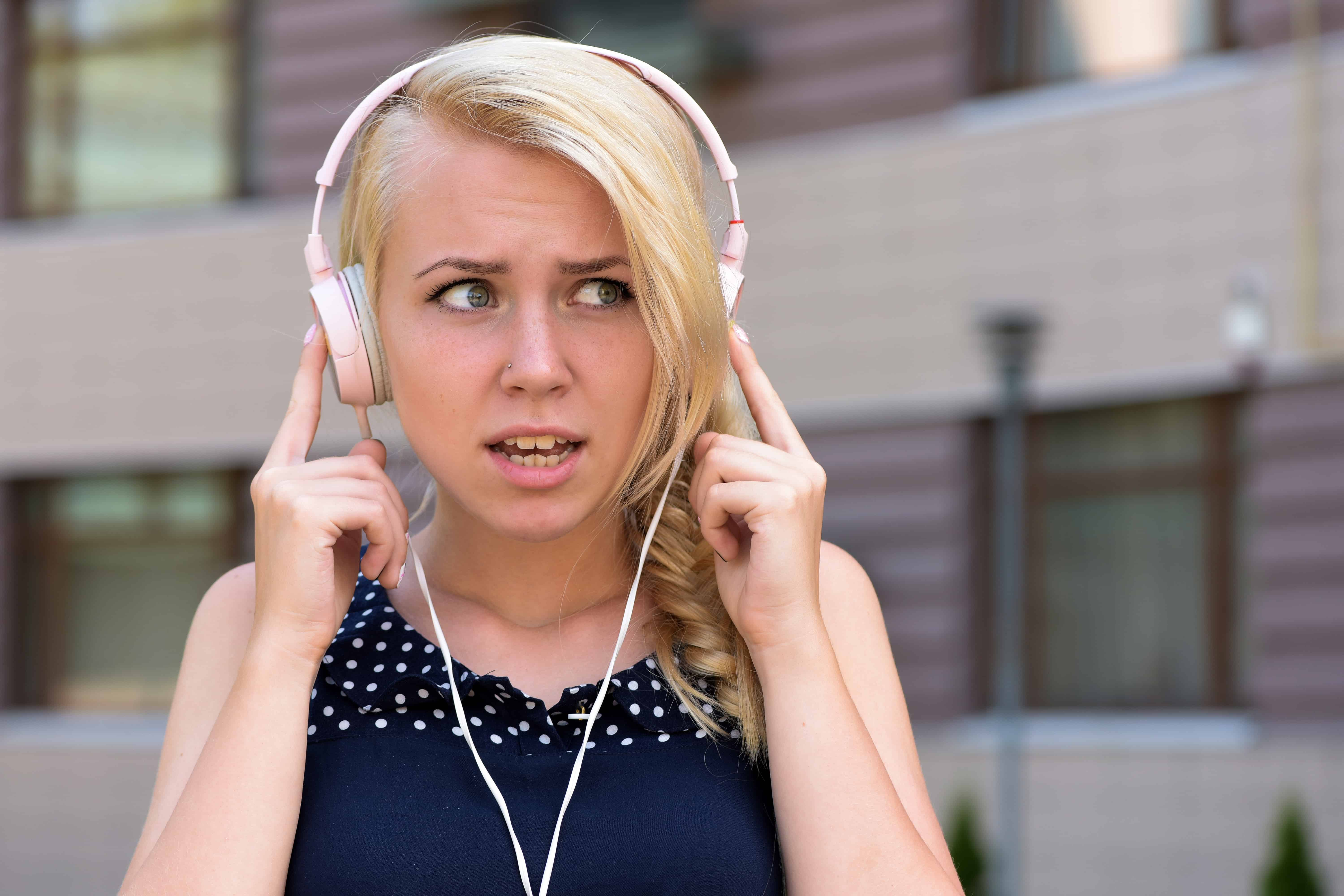 A young female wearing headphones that don't appear to be working