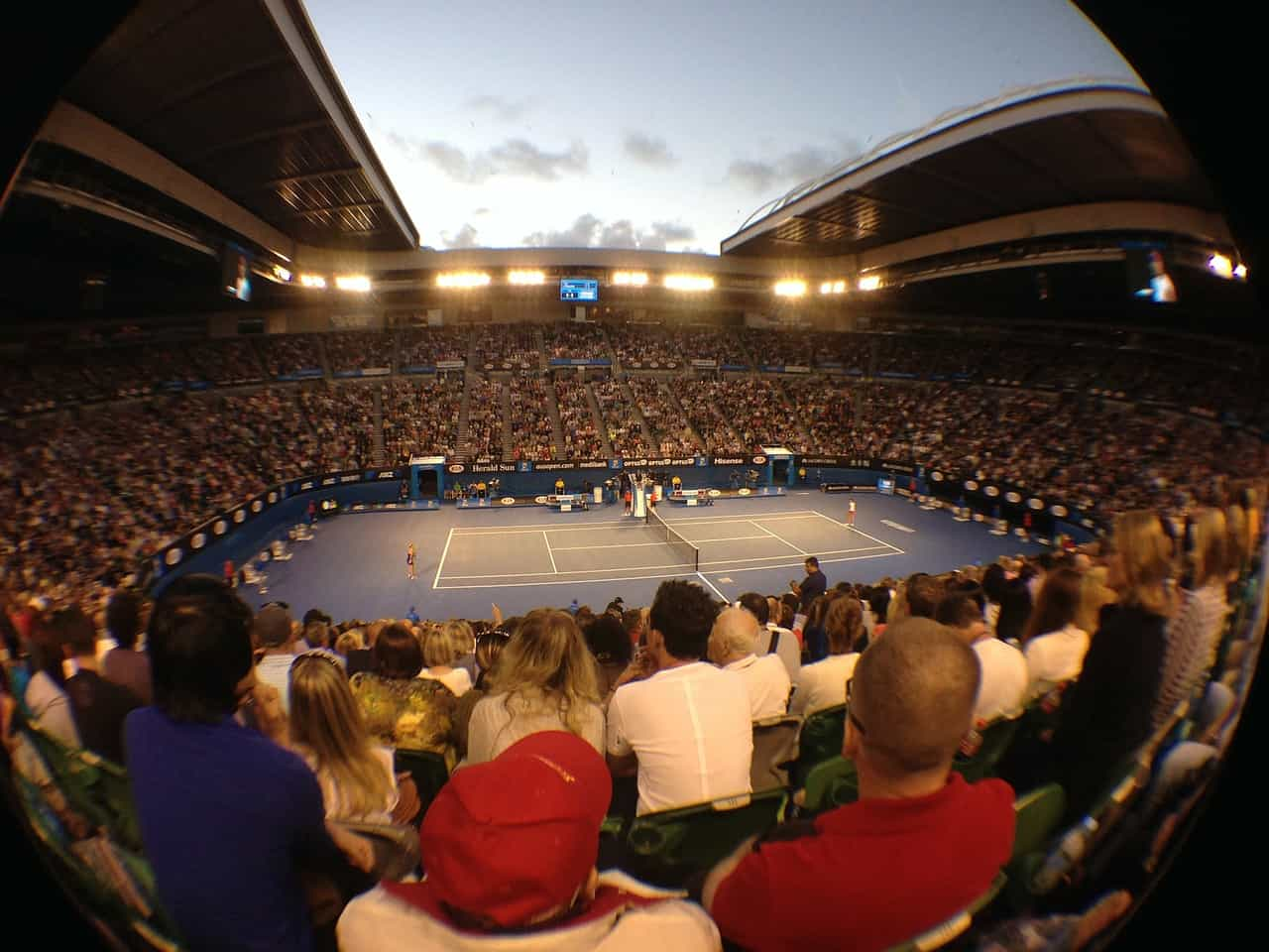 Fish-eye camera view of a tennis court and the surrounding stadium