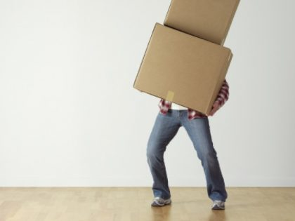 Person holding toppling boxes