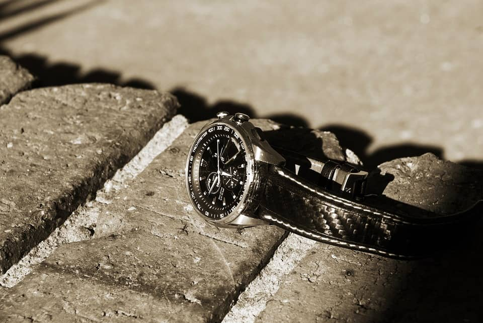 A watch laying lost on top of a wall