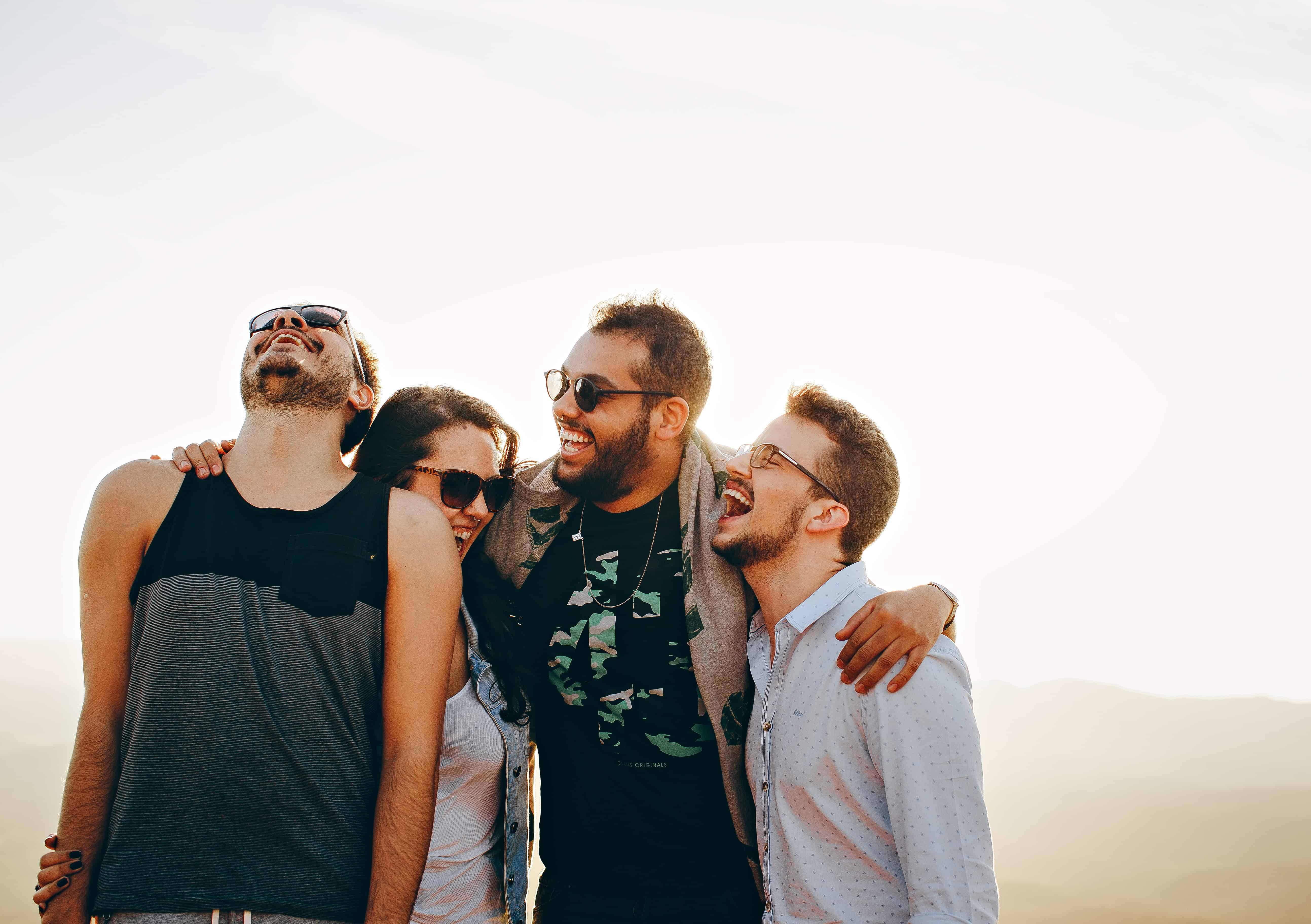 Four friends laughing together outside