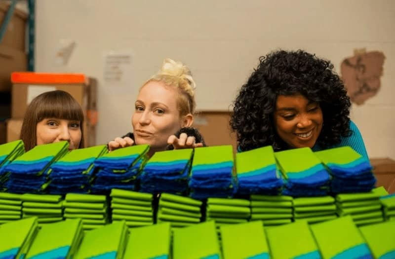 green and blue biodegradable bags with three women