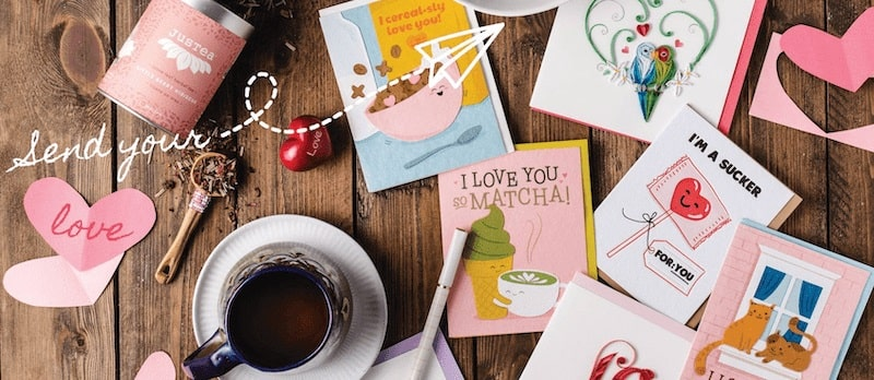 greeting cards and tea on wooden table