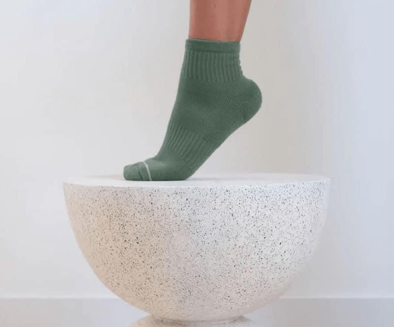 green socks stepping on stone bowl