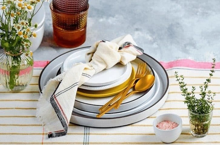 dinnerware with golden cutlery on a white and mustard striped tablecloth