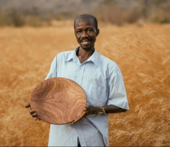 artisan holding wooden bowl in a field