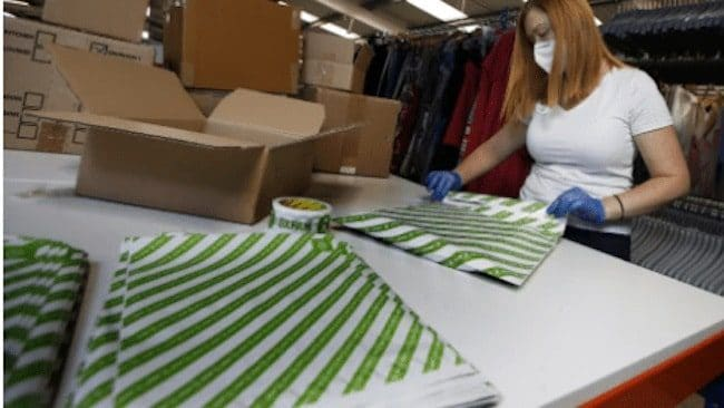 woman wearing mask packing oxfam box