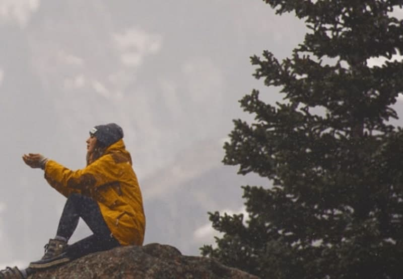 women wearing yellow jacket sitting on top of a mountain