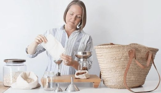woman pouring coffee beans through a funnel