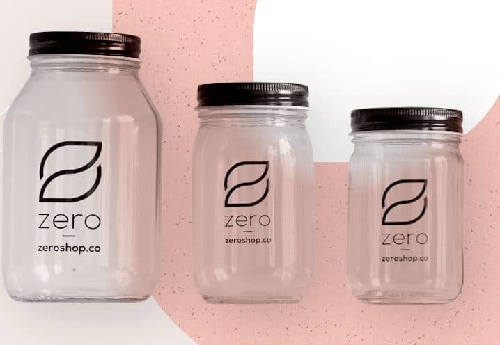 Three glass jars with pink and white background
