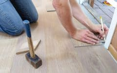 man measuring wooden floor panel
