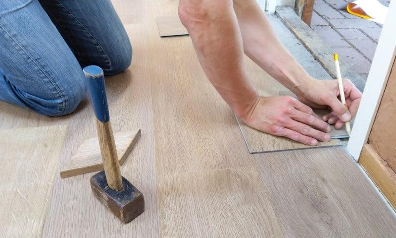man measuring wooden floor panel