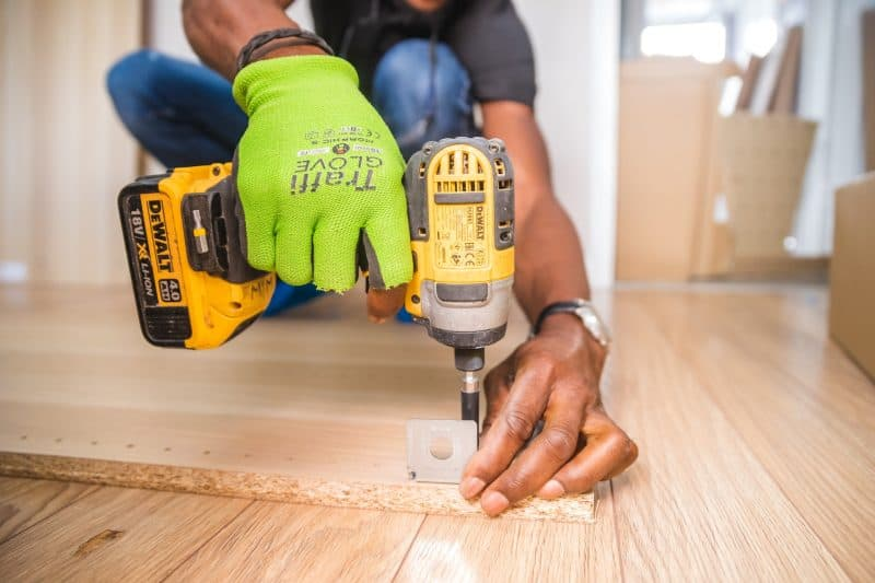 man screwing in a nail on wood with yellow and black drill