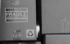 Grayscale picture of stacked boxes with one labeled 'fragile'