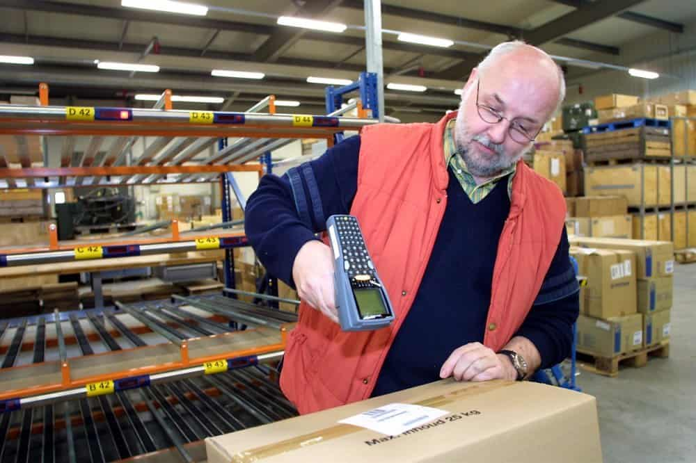 A warehouse worker scanning a barcode on a parcel
