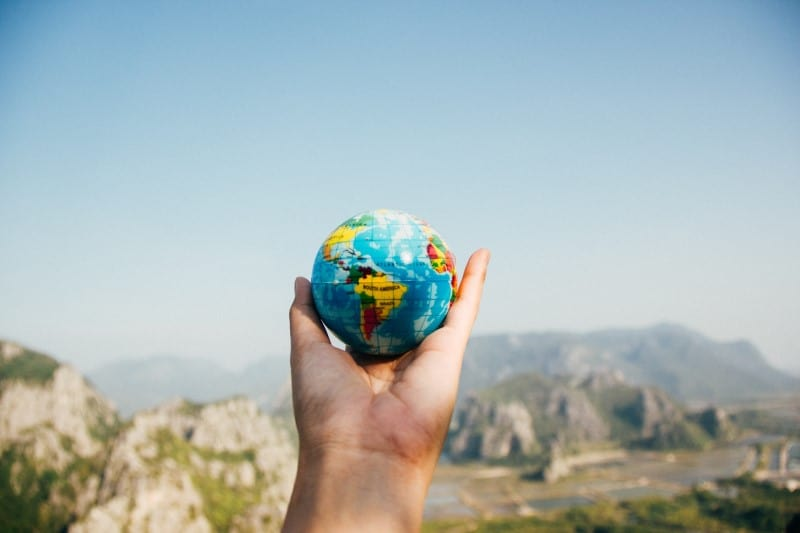 Person holding globe facing mountain
