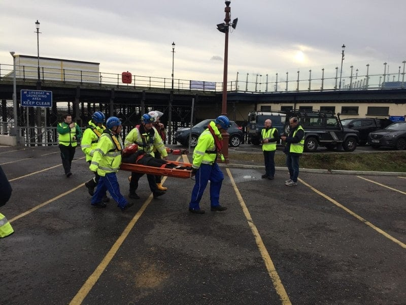 Workers practicing emergency drills while being supervised