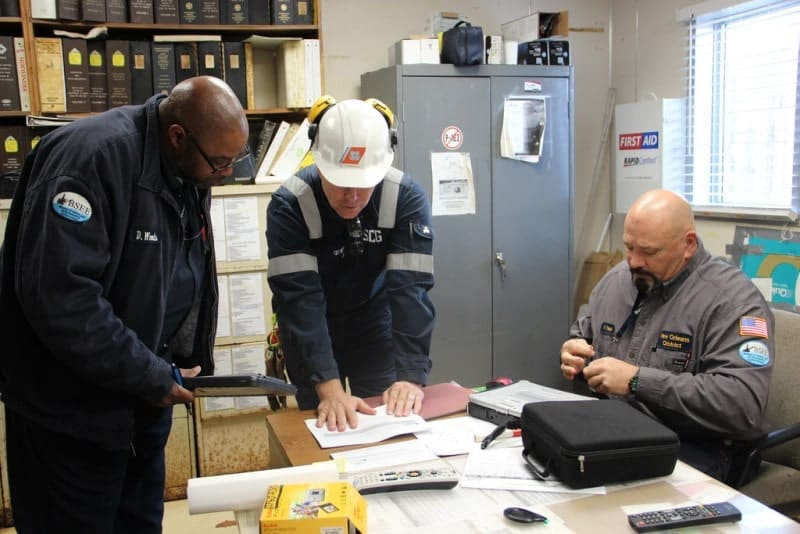 Environmental inspectors reviewing employee records